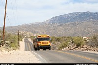 Arizona, School bus on the road, with the Santa Catalina Mountains in the background.