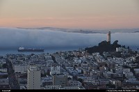 The fog is flooding the bay, literally, while another cargo is sailing to the port. Coit Tower to the right.
