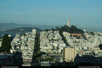 World famous Lombard Street with the Coit Tower afar. This street cross the city from the Golden Gate to the Pier. The famous portion begins here.