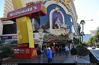 Las Vegas : Down the strip with the giant, iconic McDonald's arch anchored to the sidewalk. Harrahs Casino in the background.