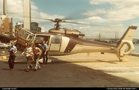 A party of happy visitors leaving an Island Helicopter SA365 Dauphin engine and rotors of which are kept running in anticipation of another circuit over New York's area.