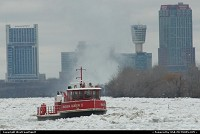 On duty boat in the Niagara River. The cloud in the background is produced by the horse shoe shaped fall. These tall building are located in Niagara Falls, Canada.