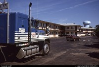 Oshkosh : Part of Motel 6. Providing for the foreground, a Peterbuilt tractor sits on the parking lot while the driver rests from long hours of driving. The blue protuding bulky structure afar is a water tank.